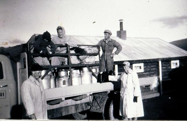 Mjølkebilen klar for avgang frå Tollevshaugen ved sekstida om morgonen, truleg ein gong på 1950-talet. Ståande på lasteplanet, sjåføren i mange år, Magne Rudiløkken. Dei andre er turister som skal vera med bilen. Og dei det ikkje er plass til inni førarhuset må sitja oppå spanna.